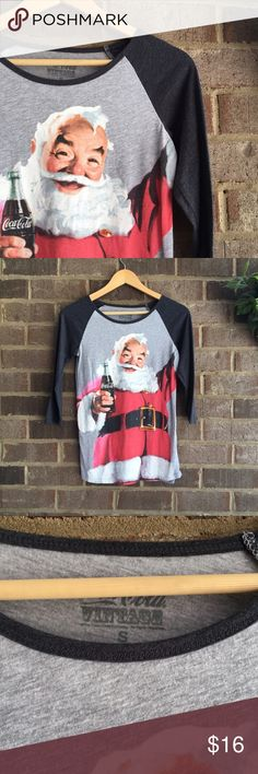 🍓BOGO Coca Cola Vintage Santa Clause Raglan Shirt Need a gift for that person who has everything? This Christmas top from Coca Cola is just the thing.  A cheery Santa holding a refreshing Coke puts a smile on anyone's face. The black raglan sleeves and heather grey background makes this more than just another brand tee. In great condition. Made from a cotton blend. Approximate measurements lying flat, 16.5 inches across the bust, 25 inches down the back. 10255 (10153) Coca Cola Tops Tees…