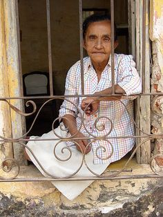 Une vieille femme à sa fenêtre dans le centre de Trinidad.