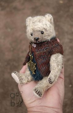 Teddy bear Poddle is constructed in mohair with wool felt pads. Fully jointed with glass eyes and a stitched waxed varnished nose. Standing approx. 6 1/4, 15.8cm tall. Wears a knitted wool/cashmere yarn jacket with rabbit charm necklace or maybe you prefer just the necklace. Firmly