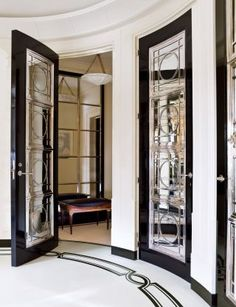 the entrance hall features ebonized-mahogany doors inset with mirror and silver-plate grillwork