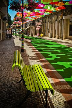 Shadows as interesting as the umbrellas. Art - live and in person.  Temporary park made with yarn-bombing, astroturf and umbrellas. Águeda, Portugal