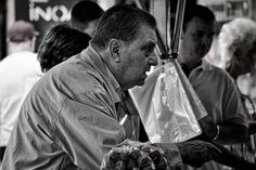 Street Photography - A market scene. Man doing his deal in the fruit and veg market in St. Feliu de Guixols, Catalonia.