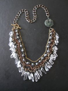 """A glittering tangle of new, salvaged, and vintage chain scraps form a sweeping bib on this one of a kind statement necklace. The bib section is accented with dark (and stormy) gorgeously luminous hematite nugget beads and a heaping handful of hand-wired, beautifully polished, crystal clear natural quartz crystal points. A big round slice of swirled green and black jasper sits at the side of the neck (such an amazingly detailed stone, my current obsession).    The shortest strand sits at 22""""…"""