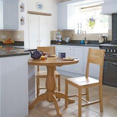 Small kitchen with white cabinetry, neutral flooring, black range cooker and wood table and chairs