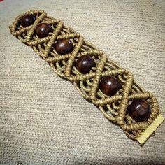 Pulseira feita em macramê com bolinhas de madeira e cordão encerado