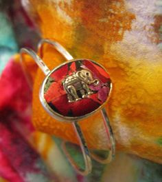 Silver tone Cuff bracelet with bezel, hand filled with pieces of metallic foiled plastic fused and a tibetan silver charm and then coated with a
