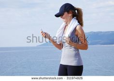 Portrait of middle age woman standing at the beach and relaxing after workout. Sporty female listening music and smiling.