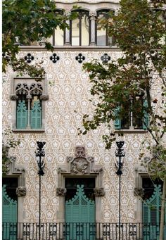 tile building exterior in Spain with Moorish influence, turquoise shutters and door, Indian, Moroccan, Islamic architecture