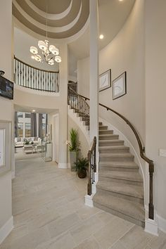 Westin Homes - Bridgeland - New Homes Houston - The Hopkins - Entry - Rotunda Ceiling - Wrought Iron Staircase - Curved Stairway - Chandelier - Wood-Like Tile - Architectural Detail