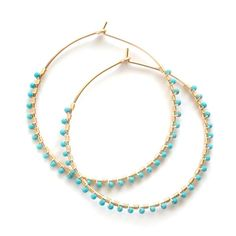 Handmade hoop earrings are wire wrapped with tiny 2mm turquoise beads. Available in 14 karat gold-filled or .930 Argentium silver in two stock sizes: Small - 1.5 inch (3.18 cm) diameter Large - 2 inch (5.08 cm) diameter Custom sizes and solid yellow or white gold are available on request. Please contact us for a quote.