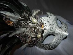 Shades of silver to black adorn this masquerade mask. Filigree metal, pearl, crystal and feather accents complement perfectly.