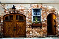 brick, door, carriage garage door with light above and window box....