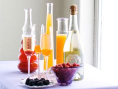 Set up a Bellini bar with fresh fruits, champagne and bottles of fruit purees. Make your own purees or purchase them in the ice cream section of the grocery store. Fill one third of a glass with the puree; try orange, peach or raspberry. Add two thirds of chilled champagne or sparkling wine, and serve immediately.