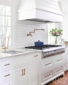 white kitchen with marble subway tile and tile backsplash over stove on