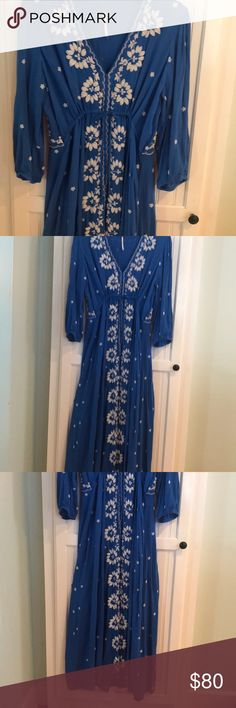 """Free People royal blue with embroidery maxi dress Free People royal blue maxi dress with white embroidery across most of the dress. V neck with a tie under the bust to cinch and tie to your size. In the front the dress has hooks & eyes for clouded. 3/4 sleeve. Length  51 inches with a very slight up & down bottom hem. About 2 -2/12 in. I love this dress it's been my """" go to dress"""" for the last 2 years. So I don't want to wear all the time another year. Probably my friends think so to! Free…"""