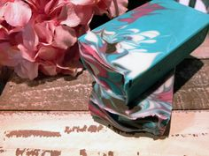 This luxury handmade soap is scented with the beautiful floral bouquet of Cherry Blossom, Jasmine, Lily of the Valley and Freesia resting on base notes of powdery Musk and precious woods. This soap is enriched with pure Silk and Cocoa Butter and poses a delicate pink, white and copper brown swirl in our signature teal base. Intensly feminine and positively happy!  Net weight: 100g   <h5></h5>