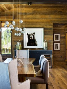 From floor to ceiling, the entire dining room features rustic, exposed grain wood. Strong statement pieces, like a navy blue buffet, mirrored chandelier and even a simple bear portrait, are used to break up the wood. The comfortable dining room is made of a wood slab table, gray bench seats and slipcovered armchairs.