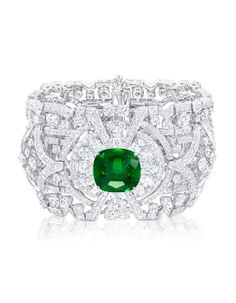striking cuff bracelet, with a strong design aesthetic conjuring the sophisticated and distinctive Art Deco era. Three vivid Colombian emeralds of the finest quality are centred on a bold geometric formation of scintillating diamonds, which curve effortlessly around the wrist.  Diamonds 62.75cts, Emeralds 25.47cts