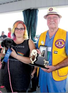 Ringmaster Lion Jess Duncan presents a trophy to Elizabeth Adelsperger and her toy poodle, Shadow Star. She was the senior winner of the Lions Club's