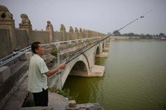 A fisherman casts his line from the Marco Polo bridge, or Lugouqiao, in west Beijing on September 3, 2013.