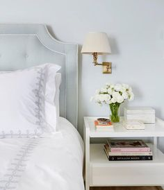 A blue gray tufted headboard accented with white piping stands on a bed dressed in white and gray embroidered bedding placed next to a white nightstand illuminated by an antique brass swing-arm sconce adorned with an ivory pleated sconce.
