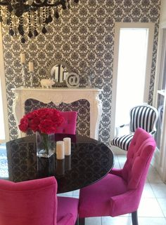 Gorgeous!! pink and black living room, cream antique mantle, velvet pink chairs, black and white cream demask wallpaper, black lacquered tulip table, black and white striped chair