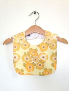 Love the gentle yellows in this new bib. Anyone know what the flower is? £7.00