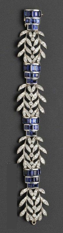 A Late Art Deco Platinum, Sapphire, and Diamond Bracelet, Seaman Schepps, c. 1940s, channel-set with fancy-cut sapphires joined by diamond foliate plaques, lg. 7 in., signed. #Schepps #LateArtDeco #bracelet