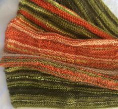 """Shades of green and orange are combined in this unique, soft rug - ideal for baby wrap, as a knee rug in winter or to take in the car for extra coziness on cool evening outings. It's quite big and stretchy, but folds into a small cushion size for storage.  A """"little brother big brother"""" item in the bronzart portfolio. Lovingly handcrafted by Bronwyn Angela White in a pet-free and smoke-free environment.  #littlebrotherbigbrother #handknit #kiwimade #nannaknits #naturalfibre Green And Orange, Shades Of Green, Small Cushions, Angela White, Baby Wraps, Main Colors, Free Knitting, Brother, Environment"""