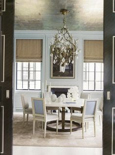 Roman shades are really well done, and their casual look is an interesting counterpoint to the crystal chandelier and the silvery wallpaper on the ceiling.