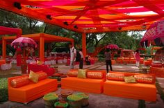 Vibrant mehendi decor , floral umbrellas , orange boulsters