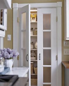 """Frosted-glass inserts in the doors obscure what's inside so the pantry doesn't have to be kept tidy. Plus, the doors add a light and bright element to the kitchen."""