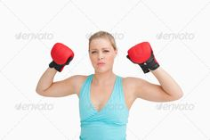 Woman rising her gloves against white background ...  20s, Looking At Camera, arms, attentively, blonde, blue, blue eyes, boxing, caucasian, competition, concentrated, copy space, earnest, fair hair, female, fighting, fists, focused, gloves, hands, health, hitting, light eyes, light hair, punching, raised, red, serious, sport, sportswear, stern, thoughtful, tied hair, white background, woman, young adult