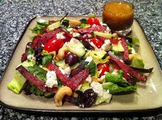 Not Your Average - Greek Salad   Ingredients 1 Large Head of Romaine Lettuce 12 Slices of Peppered Salami 2/3 Cup Grape Tomatoes  1 Avocado 1/3 Cup Red onions 1/2 Cup Kalamata Olives 1/2 of a Large Cucumber 1/2 Cup Feta Cheese (I used Athenos Tomato Basil Feta) 1/2 Cup Whole Lightly Salted Cashews