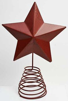 """11.5"""" Primitive Distressed Barn Red Metal Star Tree Topper $8.99 Item# T0630 Primitive barn red metal star on spring base. Metal barn star can be used as a primitive country Christmas tree topper, centerpiece, or shelf sitter. The coil spring base of this tree topper allows it to stand upright. Perfect for year round country primitive decorating."""