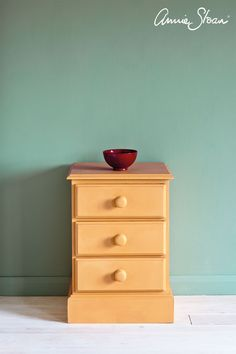 Classic pine side table painted with Chalk Paint® by Annie Sloan in Arles, a rich, glowing yellow. Set against a background of Duck Egg Blue, greenish soft blue.