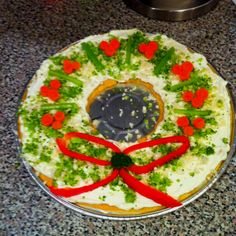 A holiday twist on the classic veggie pizza. The ribbon is red peppers, holly is broccoli florets, and the berries are carrot slices.