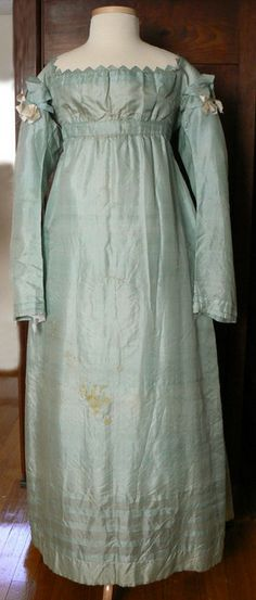 Special Occasion Dress: ca. 1815-1820, hand-stitched, plain weave silk, very high waist, long tubular sleeves (would have been worn slightly ruched on the arm), skirt is three panels and slightly gathered in front and pleated in the back, Vandyked neckline, trimmed with ribbon bows.