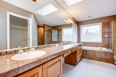 This bathroom features a marble vanity and tiling, glass-enclosed shower, and skylight.
