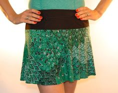 """SwingStyle PeacockEmerald Sister to all the other Peacocks, Emerald is a beautiful lightweight skirt with variations of green and green sequins.  Black wicking anti-ride undershorts feature our 5X5"""" pockets and the reverse flat-feld seams help to resist chafing! The 12"""" zippered pocket in the waistband can be worn in the front or back!"""
