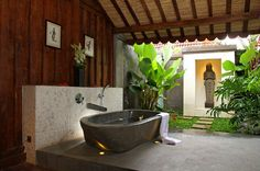 Why Is There a Bathtub in the Backyard?  This backyard bathhouse has Javanese reclaimed wood, an uplighted tub and a mini garden. A stone figurine watches over the bather.
