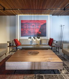 This formal lounge room has a minimal line chandelier, with bold red artwork and cushions adding a touch of color.