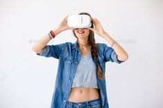 Joyful girl using VR device by arthurhidden. Portrait of loughing young woman getting experience using VR glasses on white background. Joyful female touching VR d...