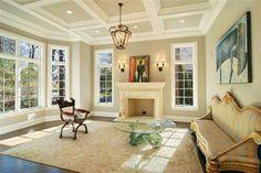 intérieur fraîs et beau, grandes fenêtres françaises, petite table ronde en verre et tapis beige