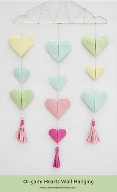 Origami Hearts Wall Hanging Tutorial With Paper Tassels is the perfect idea for DIY party decor year round. Make origami with patterned paper or a mix of metallics for a look that would be great for anniversaries, baby showers, weddings of birthdays.