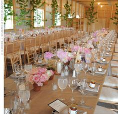 Potted peonies along with vases filled with pink and cream roses, peonies and candles lined the banquet-style tables.