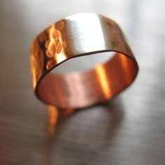 I shape the rings, fuse together the copper and silver, hammer the copper for texture and contrast, oxidize the ring using liver of sulfur, then sand and polish them to bring out the highlights. Rings are then treated with 3 coats of PermaLac jewelry grade lacquer on the inside surface to prevent further oxidization and any skin reaction to copper. Ring is 8mm wide.