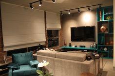 sala de estar cinza e turquesa com parede de tijolos...