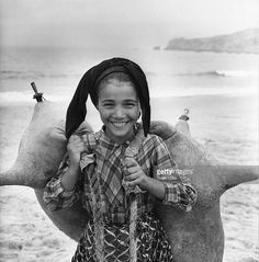 A young girl carrying waterbags on the beach at Nazare, Portugal.
