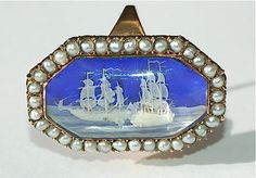 Ivory Micro-miniature Ring | High carat gold ring, circa 1798 -1800, containing a virtuoso micro-ivory carving of warships engaged in battle, with cannons blazing. The vessels are set on a cobalt blue glass ground, in an octagonal glazed compartment, within a seed pearl surround. The frigates are inscribed in sepia ink with initials T and PG, for the Spanish ship Terrible and the British ship Prince George, engaged in the Battle of Cape Saint Vincent off the coast of Portugal in 1797.